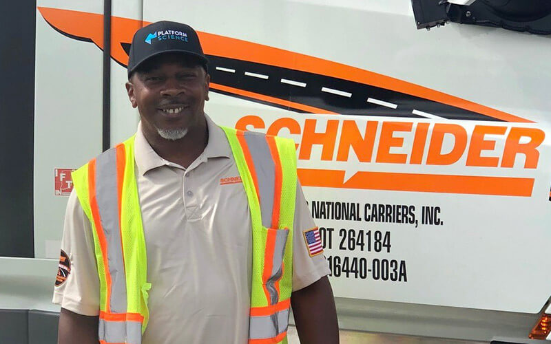 Driver Tavares McIntosh smiles while wearing a black baseball hat, tan polo shirt and neon safety vest. He stands beside a white Schneider semi-truck.