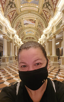 Tanaya wears a black mask and shirt and poses for a selfie in the ornate lobby of The Venetian Hotel in Las Vegas, Nevada. The lobby has a checkered floor, roman pillars and a ceiling that is covered in beautiful paintings.