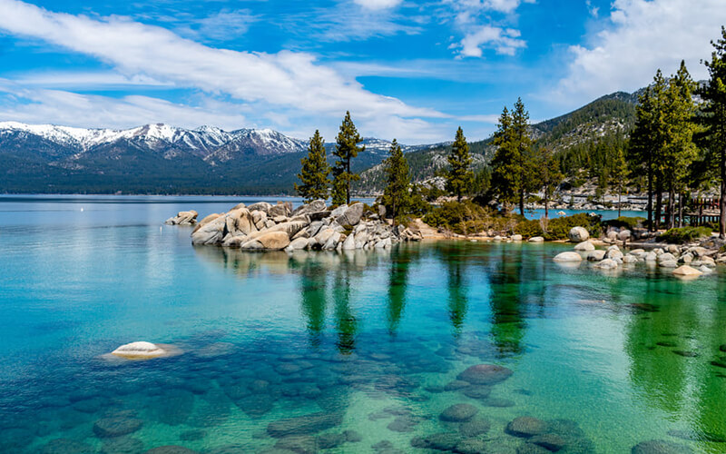 A beautiful view of Lake Tahoe includes clear emerald water, an outcropping of rocks with pine trees going out into the water and features mountains in the background.