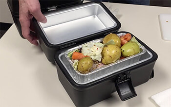 An open 12-volt portable stove contains cooked carrots, potatoes and beef.
