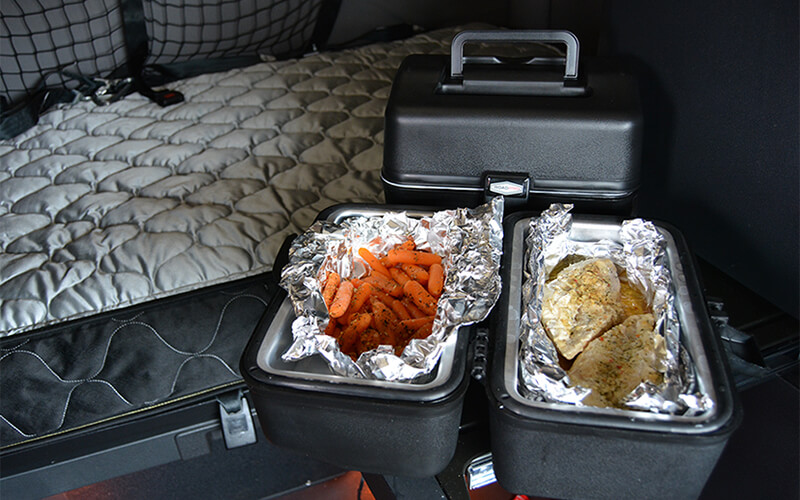 Two 12-volt portable stoves sit on a counter in a sleeper semi-truck. One portable stove is closed and the other is open and contains carrots and chicken wrapped in tin foil.