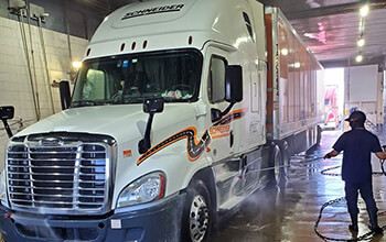 Truck wash employee shows how to wash a semi truck at a truck wash facility.