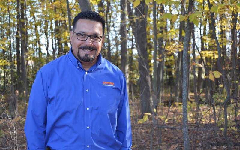 Robert Soto smiles while standing in the woods, with his hands in his pockets and wearing a Schneider button-up shirt.