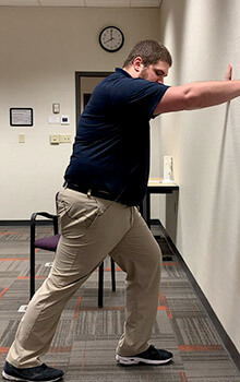 A physical therapist demonstrates stretching his leg by staggering his right foot behind his left and pushing against the wall.