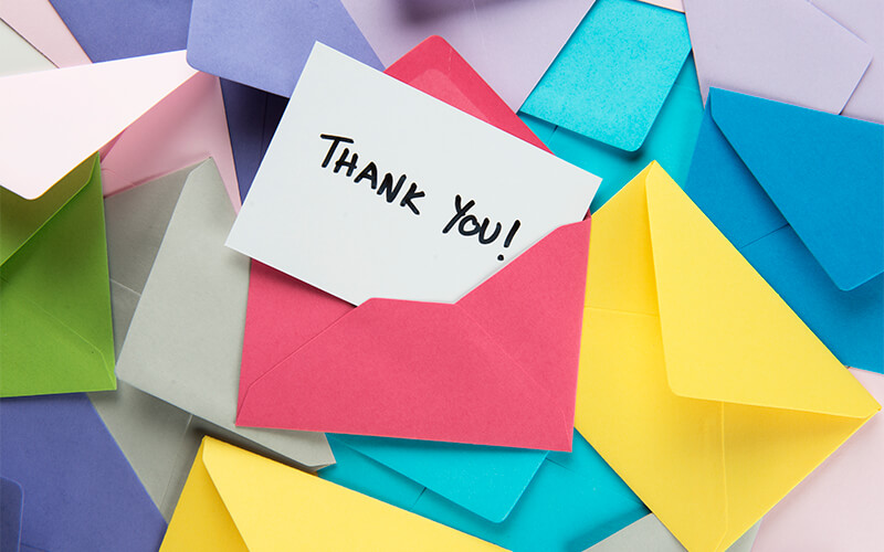 """Envelopes varying in color lay in a pile. The middle most envelope is opened and inside is a white note with the text, """"Thank you!"""""""