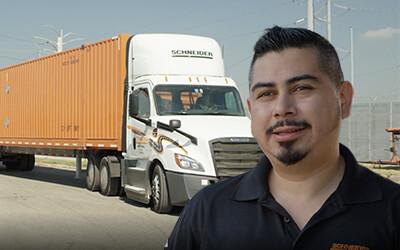 Male truck driver stands in front of Schneider Intermodal Truck