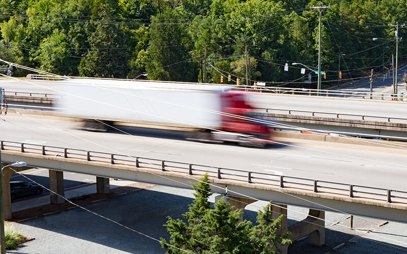 A red semi-truck hauling a white dry van container speeds by in a blur on a highway overpass.