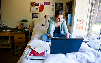 A young woman sits on her bed in a college dorm room with a laptop, book and notebook in front of her.