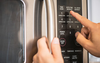 Someone holds the handle of a closed microwave door while they press the buttons on the microwave.