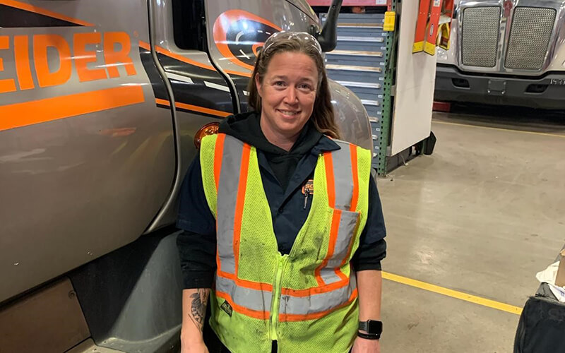 Marysa Wright, a Senior Service Advisor at Schneider who works in the Gary, Ind. shop, stands next to a Schneider tractor.