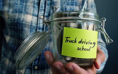 "A man in a plaid shirt holds an open jar with money in it. There is a sticky note on the front that says ""truck driving school."""