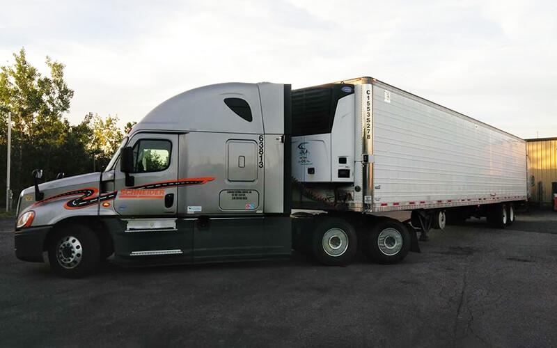 A grey Schneider semi-truck backs a white reefer trailer towards a loading dock.