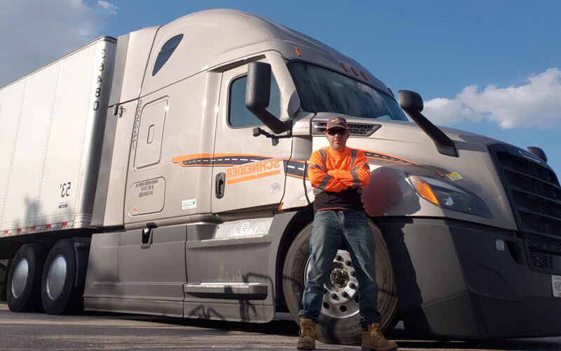 Joel Torres-Sanchez, a truck driver wearing a neon orange long sleeve shirt, blue jeans and work boots, stands proudly in front of his brand-new grey 2022 Freightliner Cascadia semi-truck.