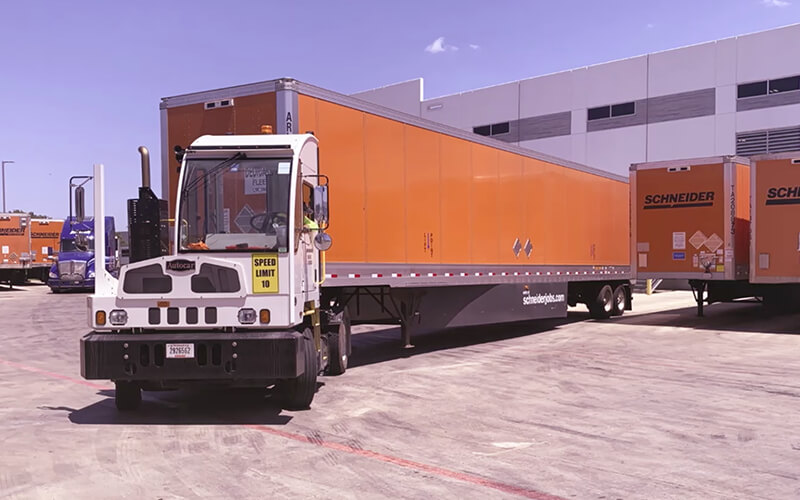 A driver uses a white terminal tractor to back an orange Schneider trailer into a tight trailer parking spot in a facility yard.