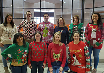 The Marketing Team gets into the holiday spirit by wearing ugly Christmas sweaters.