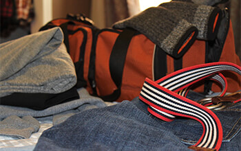 Stacks of clothes and an orange duffel bag sit on a bed.