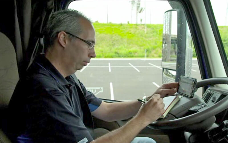 A Schneider driver writes down his load assignment on a notebook while looking on his phone.