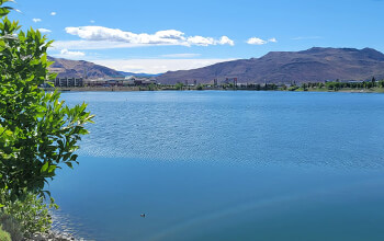 The bright blue waters of the Sparks Marina appear calm and tranquil. The city of Sparks, Nevada and mountains are seen in the distance.