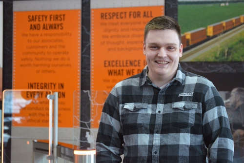 John Konicek, wearing a black, white and grey plaid shirt, poses in front of a wall in a Schneider building.