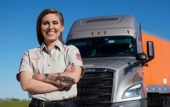 KayLeigh McCall stands in front of her Schneider truck and trailer with her tan training engineer shirt on.