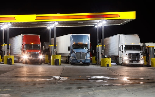Three semi-trucks are parked next to fuel pumps at a truck stop.
