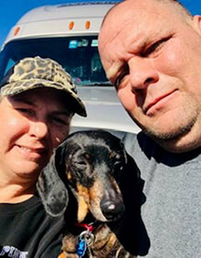 Team drivers, Rhonda and Calvin Foreman pose for a selfie in front of their grey Schneider truck with their black and brown Dachshund, Harley. Rhonda wears a cheetah print baseball cap and black shirt. Calvin holds Harley while wearing a grey t-shirt.