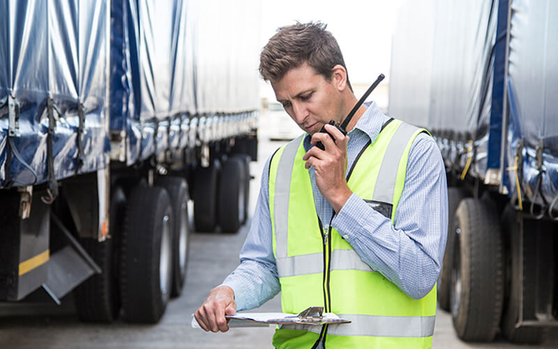 A man in a dress shirt and safety vest talks into a Walkie-Talkie while holding a clip board and standing between two tractor-trailers.