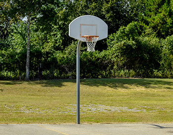A basketball hoop with a white backboard and orange hoop sits unused at a public basketball court.