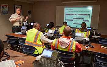 A truck driver instructor teaches new drivers in a classroom.