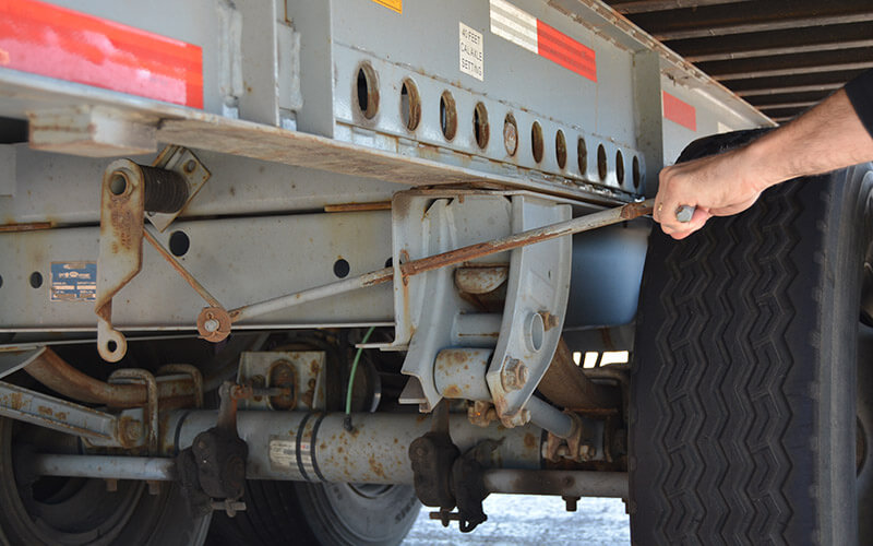 A driver's hand pulls on a handle near the rear wheels of an Intermodal container to engage the spring on the EZ Pull tandem release system of the trailer.