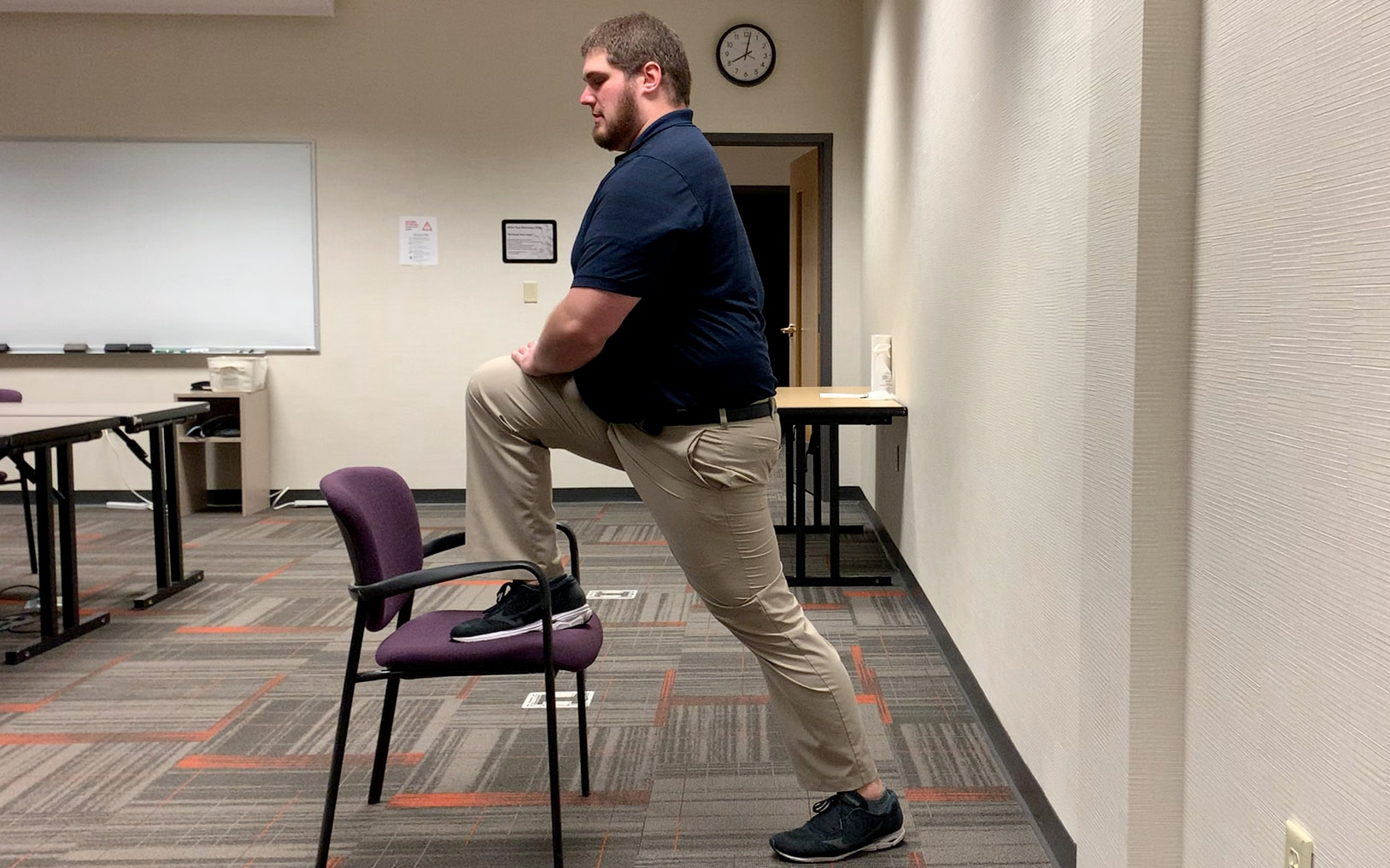 A physical therapist demonstrates stretching his quad by propping his right foot up onto a chair, bending his knee and leaning forward.