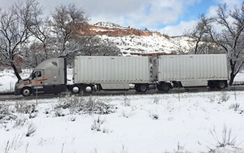 A grey Schneider semi-truck hauling two white trailers is parked at a rest area. There is snow on the ground a snow-covered mountain and trees in the background.