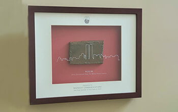 """A frame displays a square piece of steel recovered from the World Trade Center on September 11, 2001. The frame reads """"Steel recovered from the World Trade Center presented to Midwest Communications for your support in our time of need."""""""
