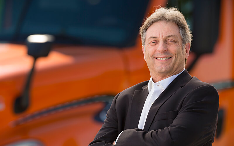 Max Pietsch smiles and stands in front of an orange Schneider semi-truck with his arms crossed.