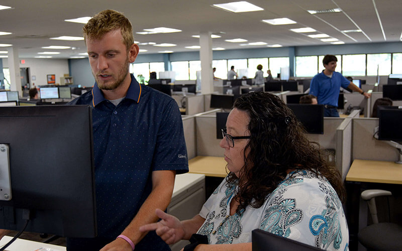 In an office setting, a man stands next to a woman who is sitting and looks at his computer.
