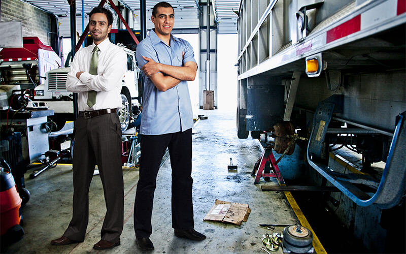 Two men standing with their arms crossed in a diesel mechanic shop next to a semi trailer. One is wearing a white dress shirt, tie, black dress pants and dress shoes and the other is wearing a blue dress shirt, black dress pants and dress shoes.