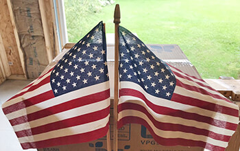 The small American Flags that Bob had attached to his truck during his trip to Ground Zero are displayed back to back in his garage.