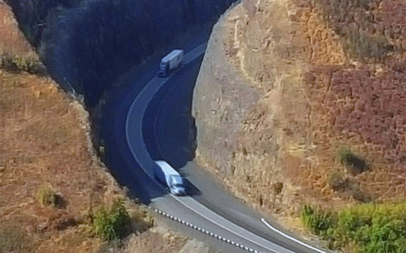 Mountain road aerial shot with 2 tractor trailers