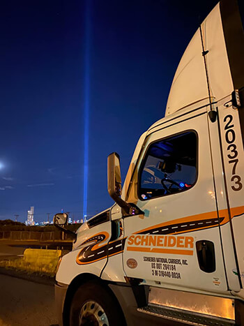 Mike Wester's white Schneider truck is parked in front of an evening display of the 9/11 Memorial lights.
