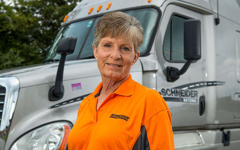 Schneider Over-the-Road driver Fay Dunn stands in front of her truck.