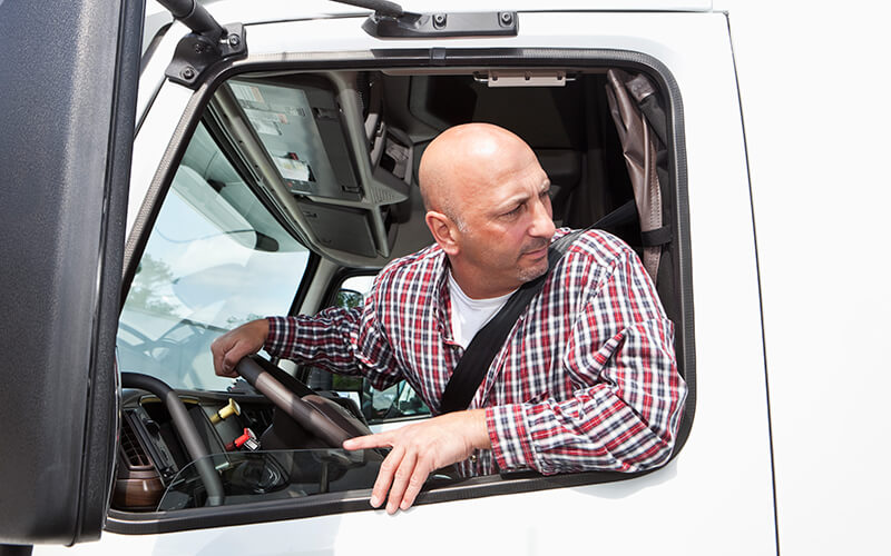 A bald truck driver wearing a long-sleeved plaid shirt looks back outside his semi-truck window.