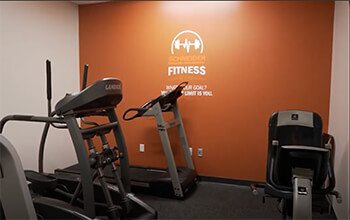 A Schneider fitness facility with a bright orange wall has fitness equipment like an elliptical, treadmill and stationary bicycle.