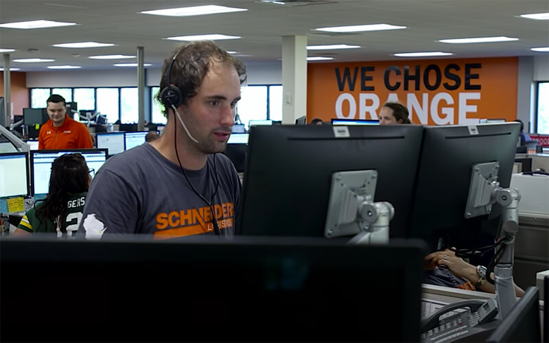"""A man wears a headset and types on a set of two monitors within an office setting. A wall behind him has the words """"We chose orange"""" on it."""