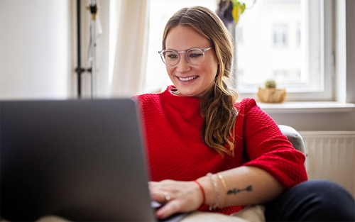 A lady with a red sweater and blue light glasses sits on a couch and works on a laptop.