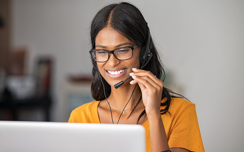 A young woman wearing a mustard-colored shirt and a headset, sits in front of a laptop and smiles.
