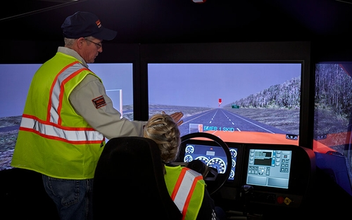 Truck driver trainer shows a driving student how to work a driver simulator.
