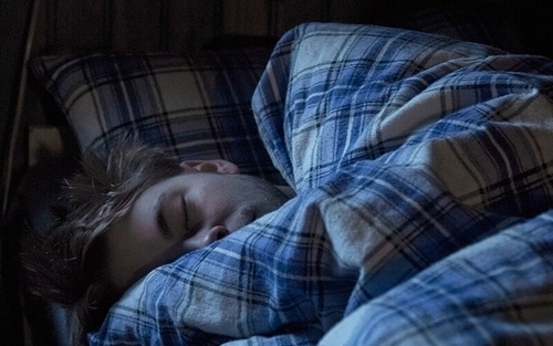 A man sleeps in a bed with blue flannel sheets on it.