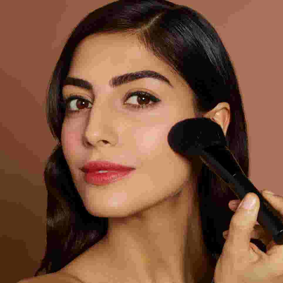 Model applying blusher using a full, fluffy powder brush. Look created by Max Factor.