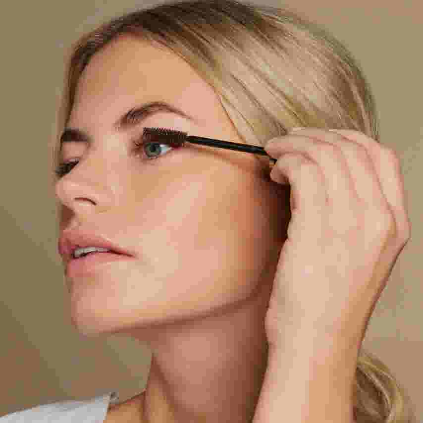 Model applying brown mascara to lashes. Look created by Max Factor.