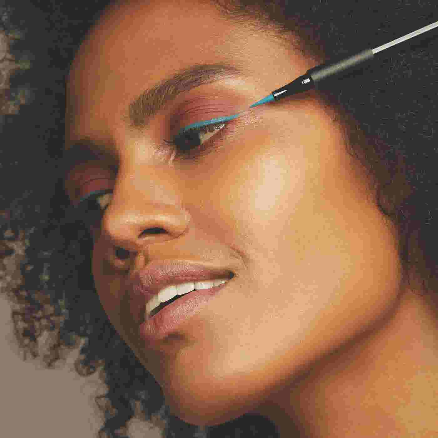 Model applying azure eyeliner for festival season